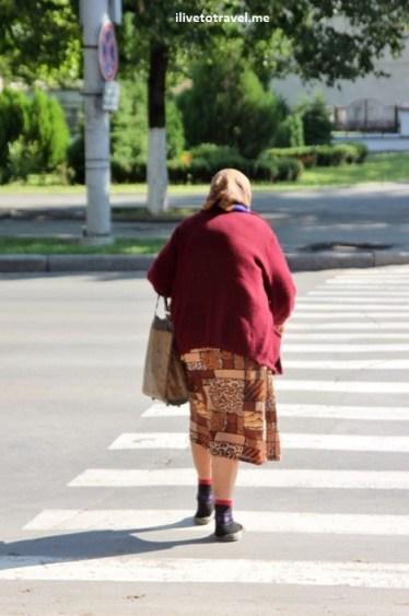 Old lady crossing Stefan cel Mare Boulevard in Chisinau, Moldova
