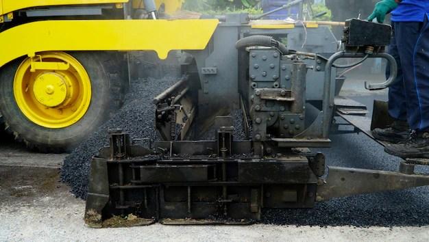 Asphalting paver machine during road street repairing works Photo