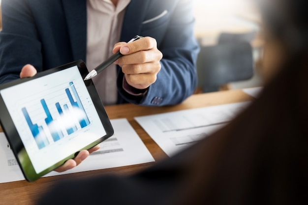 Business man and woman discuss about the financial plan on digital - business tablet