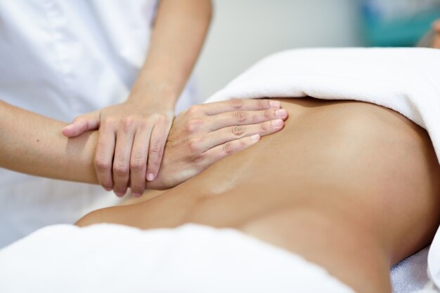 Hands massaging female abdomentherapist applying pressure on belly