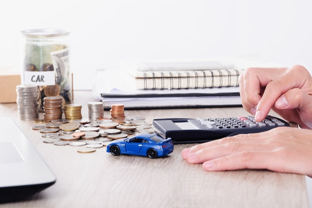 Man using calculator with car toy and coin stack for insurance loan