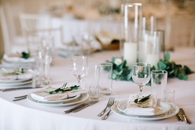 Wedding dinner table set classy white decor with greenery Photo