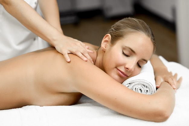 Young blonde woman having massage and smiling in the spa Photo