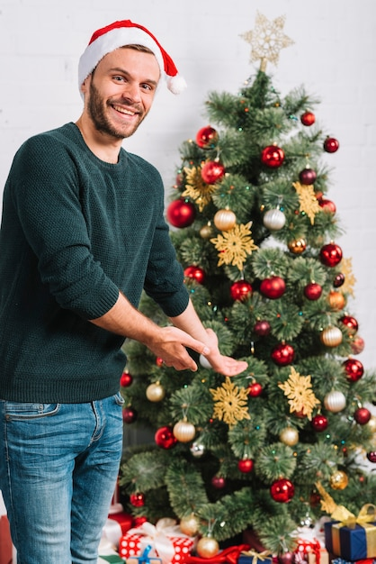 Young man showing Christmas tree Photo Free Download