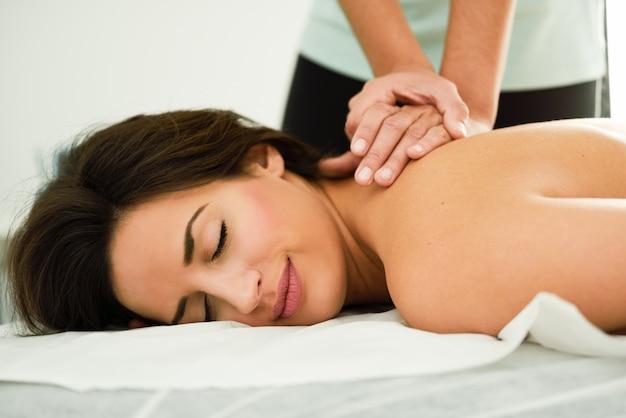 Young woman receiving a back massage in a spa center Photo Free