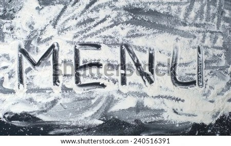 The word Menu written in flour on a wood table EZ Canvas