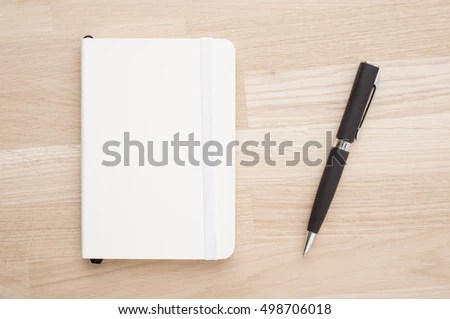 Notepad and pen lying on office desk in close up Concept of