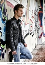 Blond Haired Young Man Standing Against Graffiti Wall Stock Photo