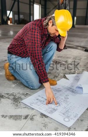 Construction Worker Safety Helmet Reading Blueprints Stock Photo