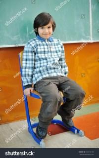 Cute Little Boy Sitting In Chair In Front Of Blackboard ...