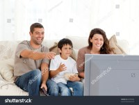 Family Laughing While Watching Television Together In The ...