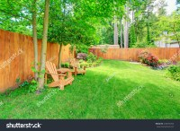 Fenced Backyard With Green Lawn, Flower Beds And Romantic ...