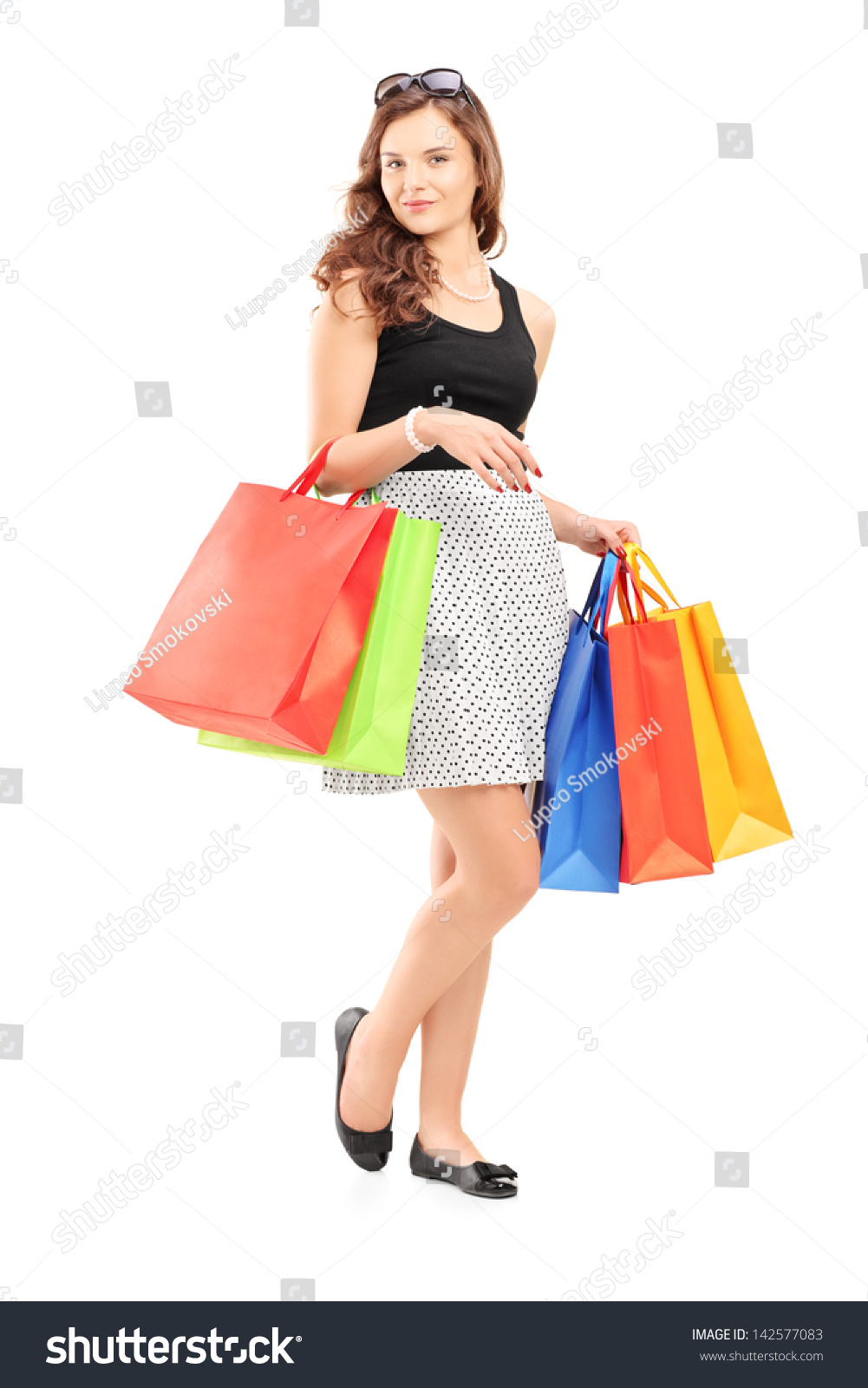 Full length portrait of a beautiful young woman posing with shopping bags isolated on white