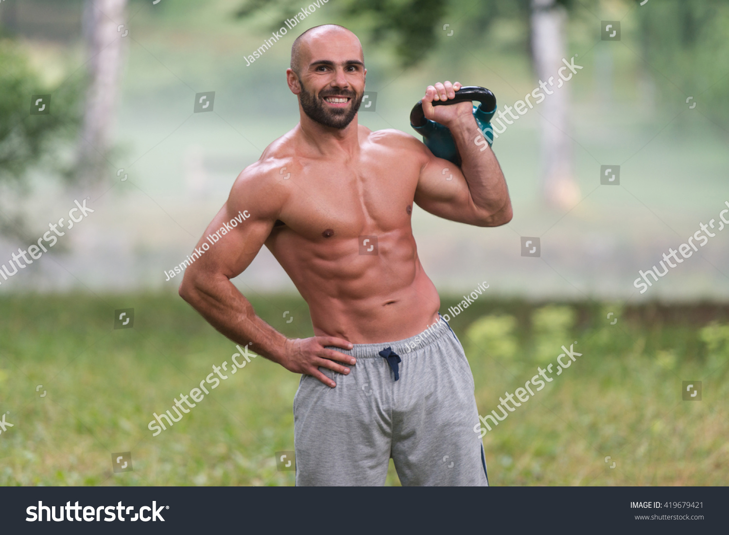 Kettlebell Bodybuilding Muscular Adult Caucasian Man Doing A Exercise Outdoors With