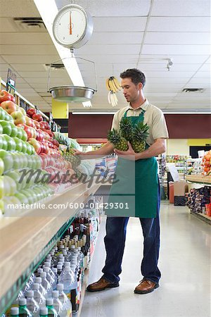 Sales Associate Stocking Shelves in Grocery Store - Stock Photo - sales associate
