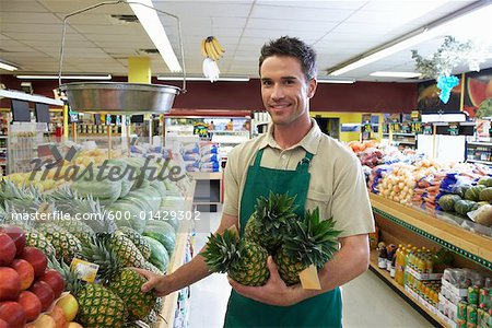 Portrait of Sales Associate Stocking Shelves in Grocery Store - sales associate