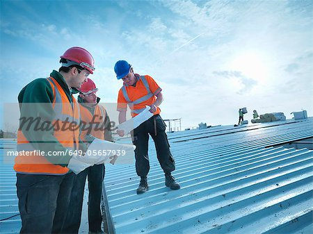 Workers reading blueprints on roof - Stock Photo - Masterfile
