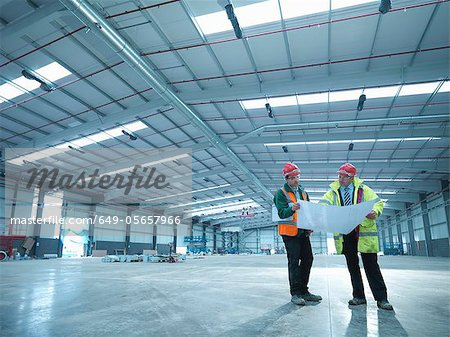 Construction workers reading blueprints - Stock Photo - Masterfile