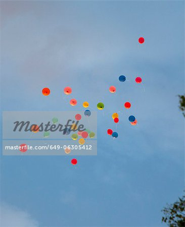 Bunch of balloons floating in sky - Stock Photo - Masterfile