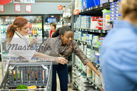 Female shop assistant helping customer - Stock Photo - Masterfile