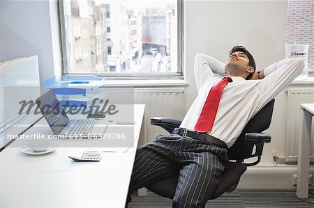 Young Indian businessman relaxing in chair at office desk - Stock