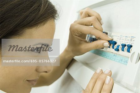 Woman pushing lever in fuse box - Stock Photo - Masterfile - Premium