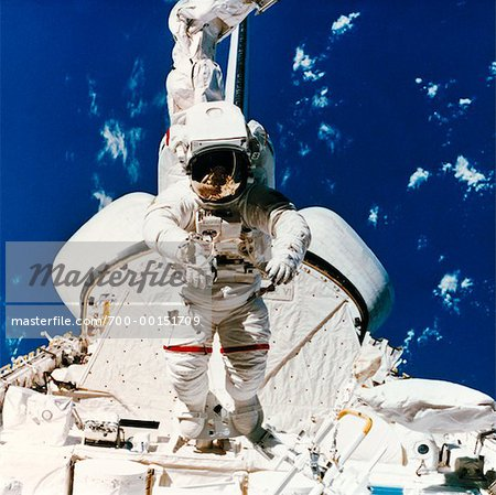 Astronaut on Space Shuttle with Canada Arm - Stock Photo