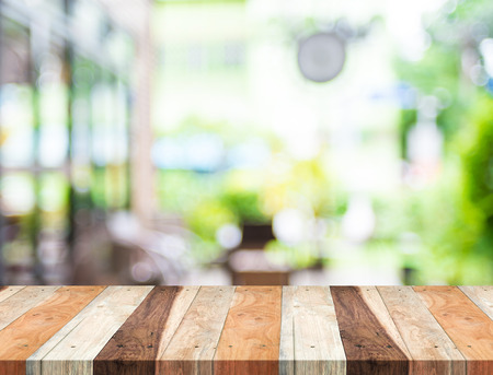 Empty tropical wood table and blurred garden cafe light background