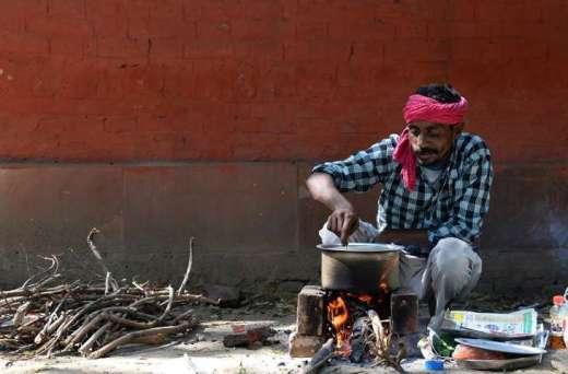 Man prepares food on sidewalk in Delhi Sajjad Huss