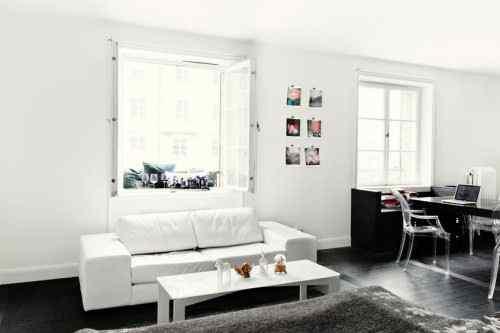 Living con mobiliario blanco y pisos negros