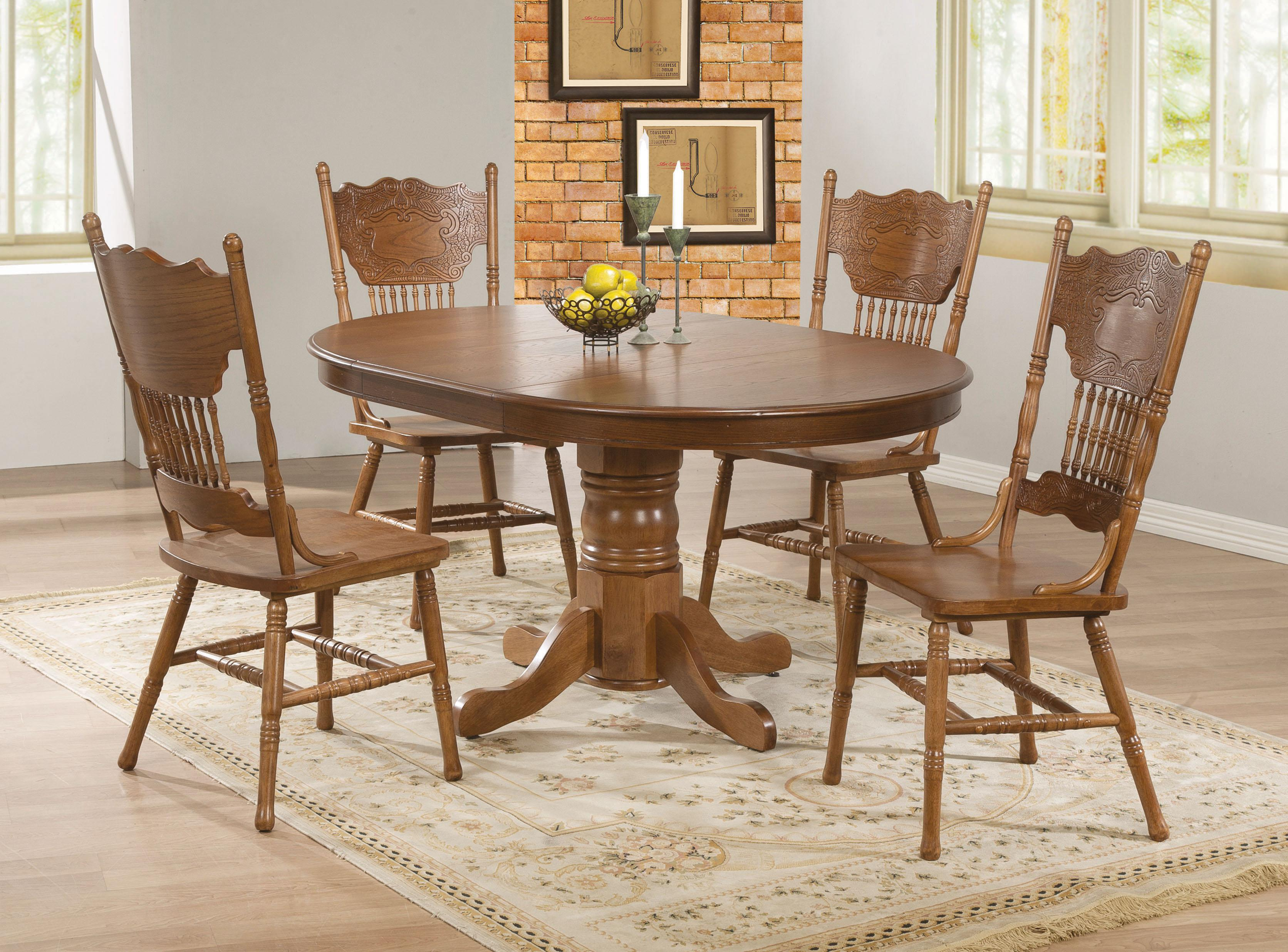 item oval kitchen table Oak Finish Round Oval Dining Table with Single Pedestal Decorative Apron Brooks by Coaster Wilcox Furniture Dining Tables Corpus Christi