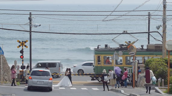鎌倉高校前で結婚式に流すためのビデオを撮影する台湾人カップル:huffingtonpost.jpより引用