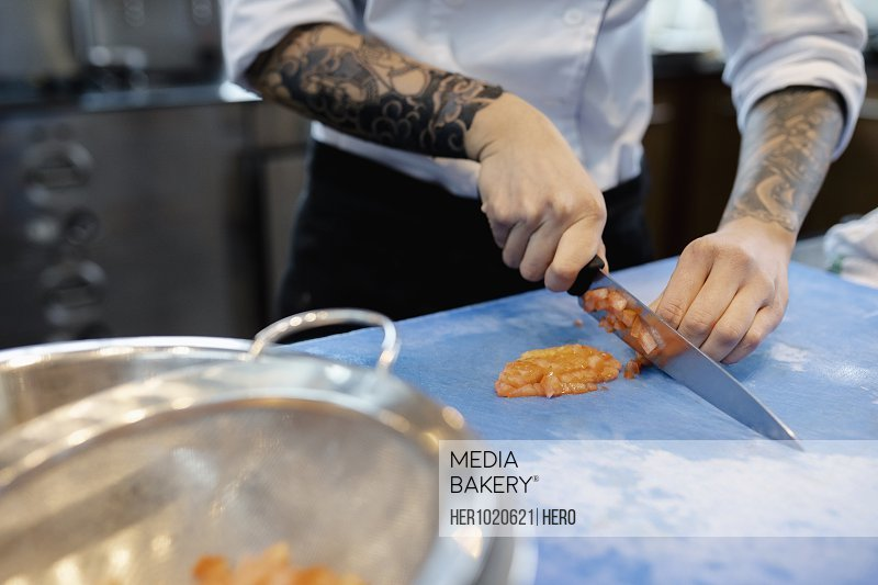 Mediabakery - Photo by Hero Images - Prep cook with tattoos slicing