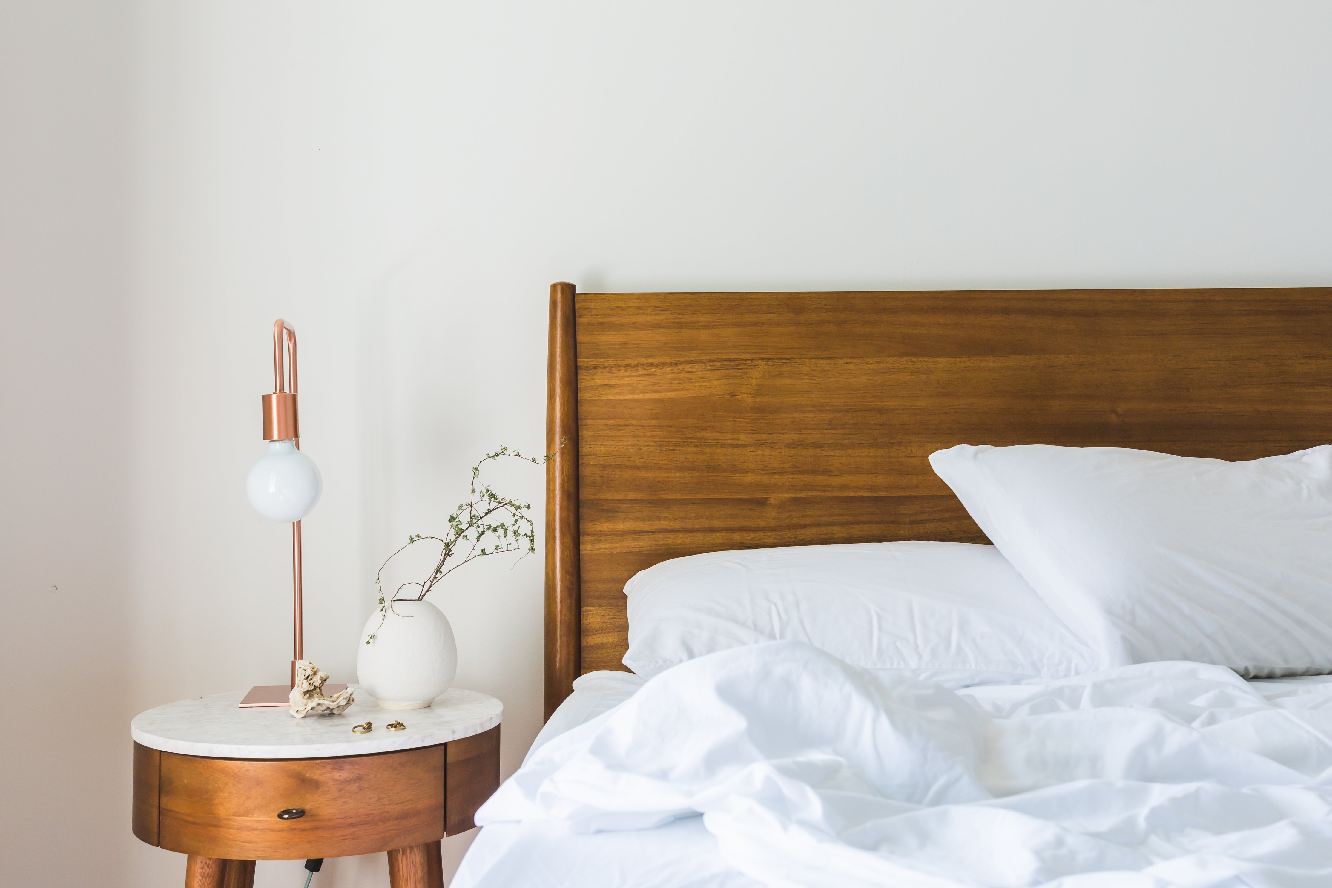 White Bedspread Beside Nightstand With White And Copper