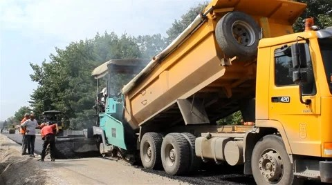 Truck pouring asphalt in machine for paving,roller flatten behind by