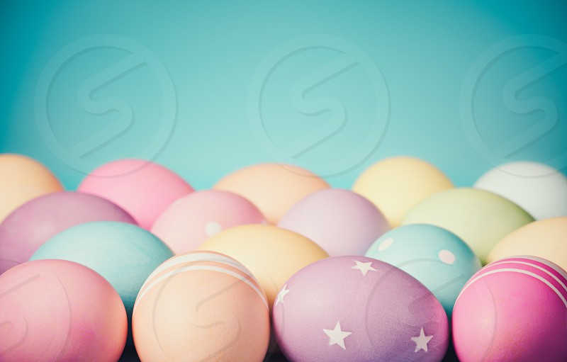 Colorful Easter Eggs border on a teal blue background with subtle