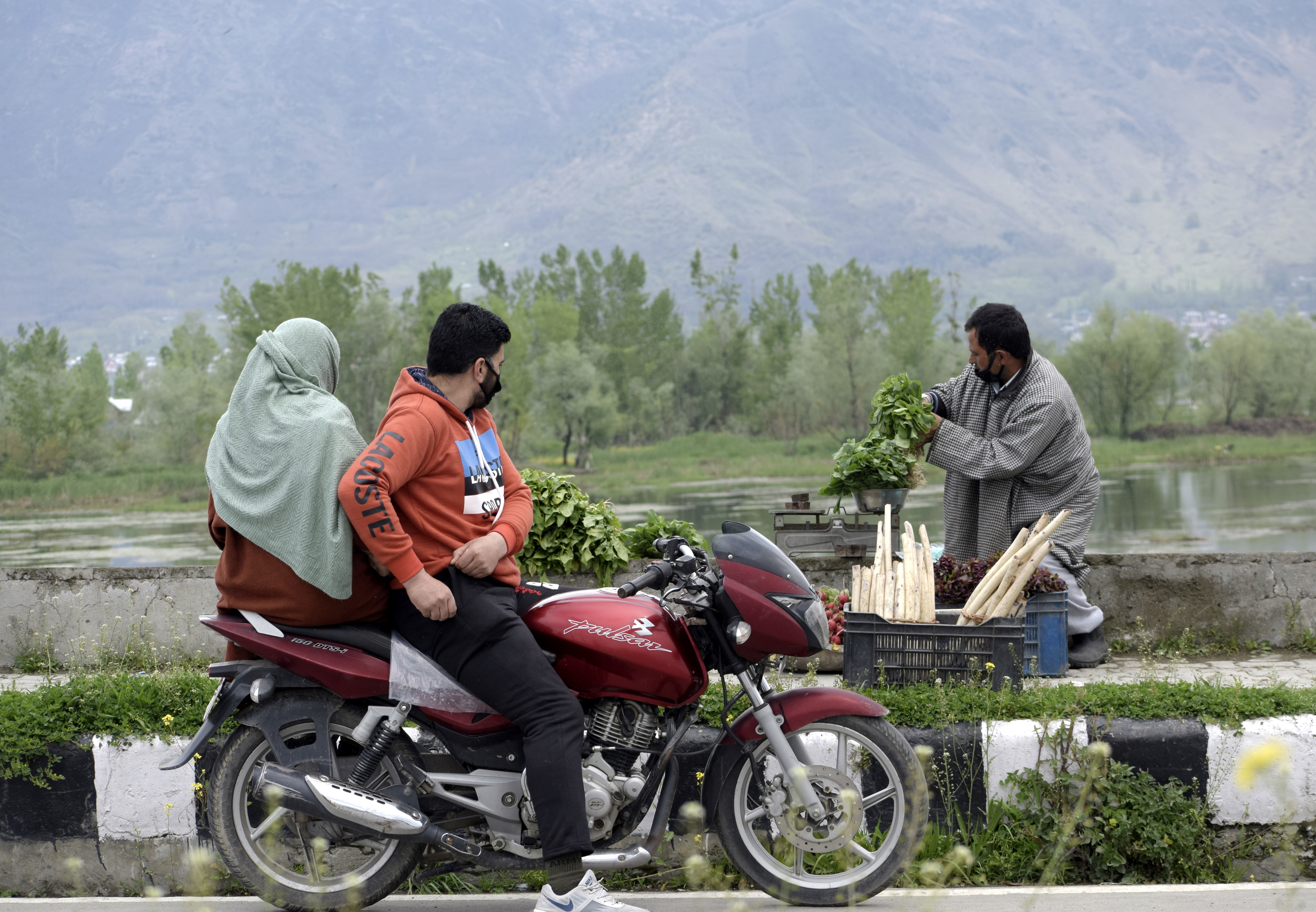 Man and woman on motorcycle near a worker and a lake