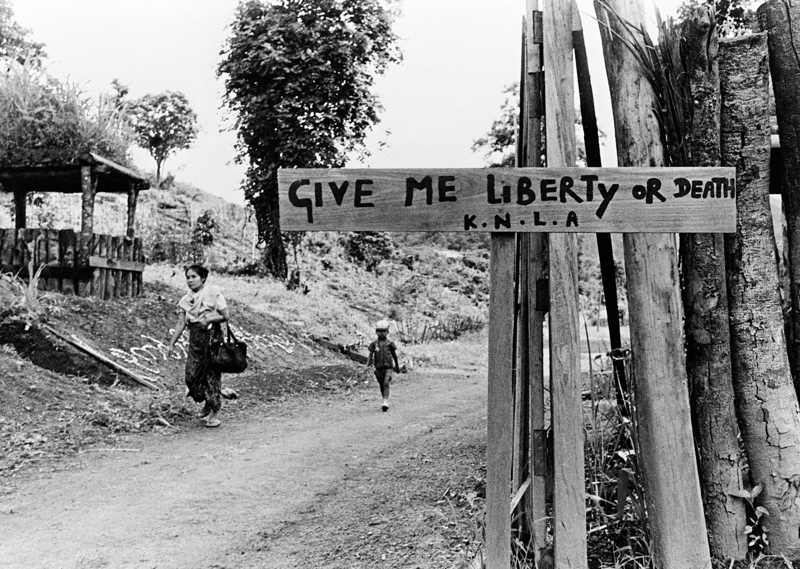 Black-and-white image of a guard hut and a wooden sign reading 'give me liberty or give me death'