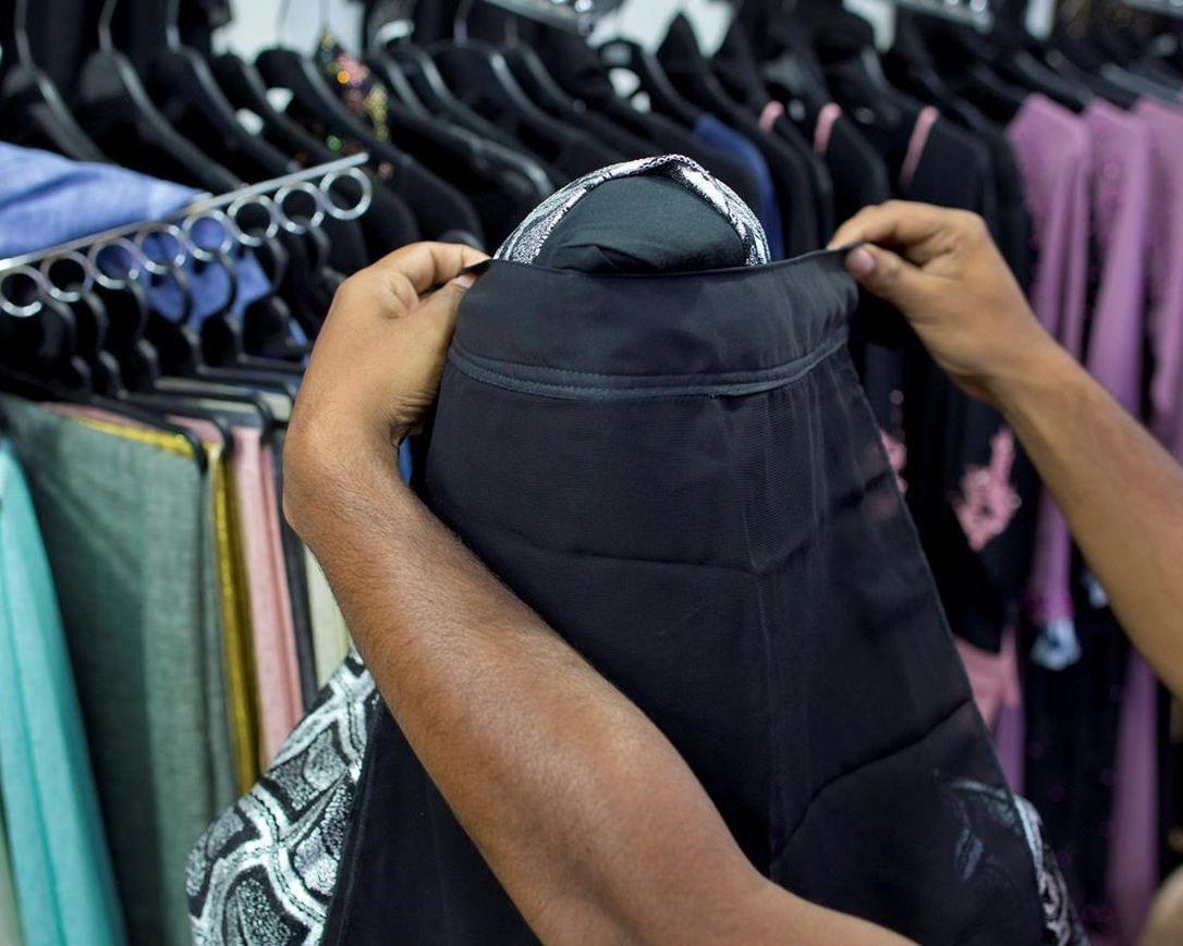 A salesman covers the face of a mannequin with a niqab cafe veil at a women's clothing shop in Kattankudy, Sri Lanka, Monday, April 29, 2019. After being targeted by Islamic State suicide bombings on Easter, Sri Lanka has banned the niqab face veil, which increasingly has been seen in Muslim areas of the island nation's east.