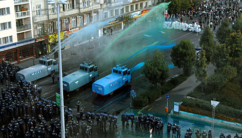 Riot police use colored water cannons Monday to push anti-government protesters out of downtown Budapest.