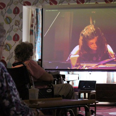 Care home residents watching a live streamed piano concert