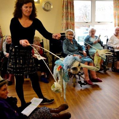 Performers with puppet and lady in top hat, performing to older people in care