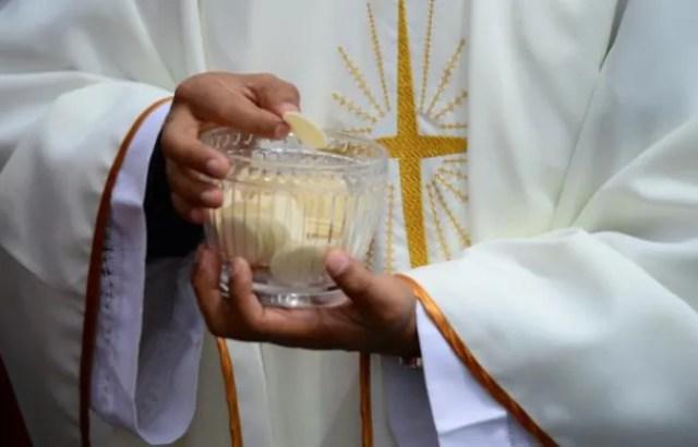 Un prêtre donne la communion le 7 juillet 2015 à Quito