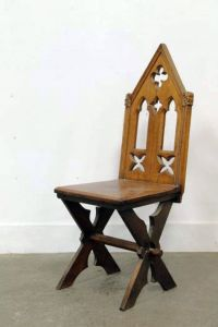 An old Medieval style oak occasional chair, with crossed ...