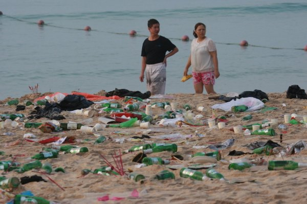 Two people are walking at the beach, looking at the garbage.