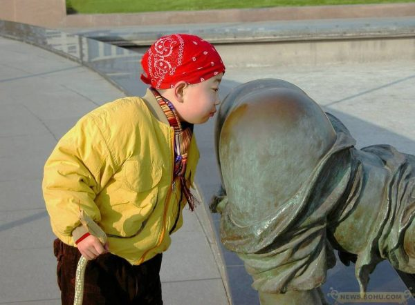 "A boy is ""sniffing"" a statue's backside."