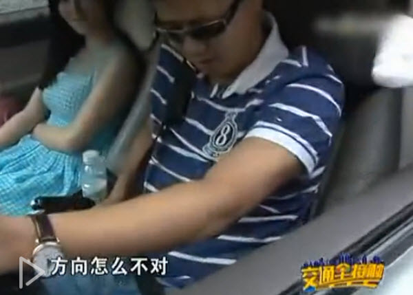 A Chinese man is stopped by traffic police for not wearing his seat belt.