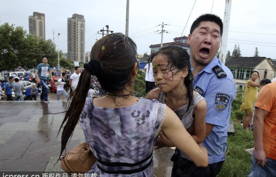 A policeman is carrying a girl to a safe place.