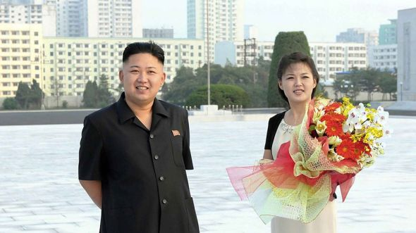 Kim Jong un and wife Ri Sol-ju with a bouquet of flowers.