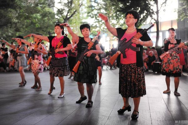 """Chinese """"aunties"""" (older middle-aged women) carying toy AK-47 rifles plaza dancing and """"fighting Japanese devils"""" on the streets of Beijing."""